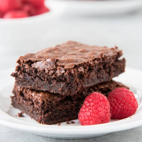 2 gluten free brownies sitting on white plate with 2 raspberries. gray background. more raspberries and brownies in background (at different angle)