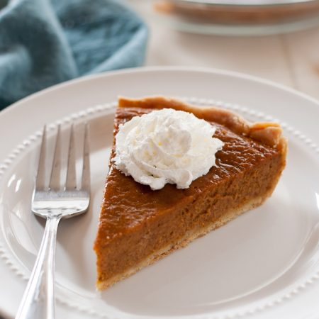 slice of gluten free pumpkin pie with dollop of whip cream on top. Fork sitting to side of pie, with blue napkin in background