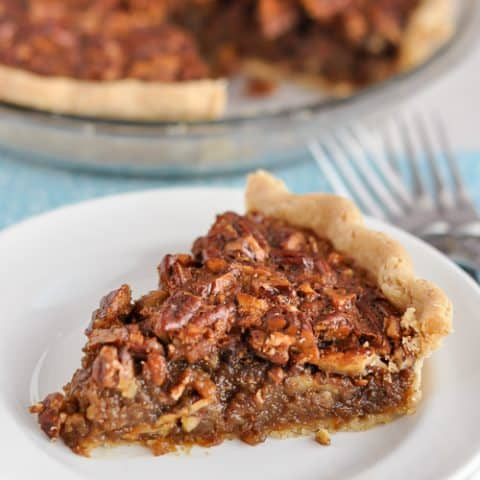 slice of gluten-free pecan pie sitting on stacked plates with cut pie in background