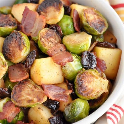 overhead shot at different angle of brussel sprouts with apples and bacon in white bowl with cream napkin with colorful stripes