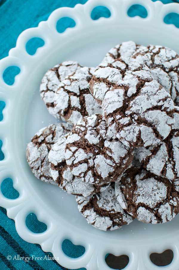 top down view of white platter piled high with gluten free chocolate crinkle cookies