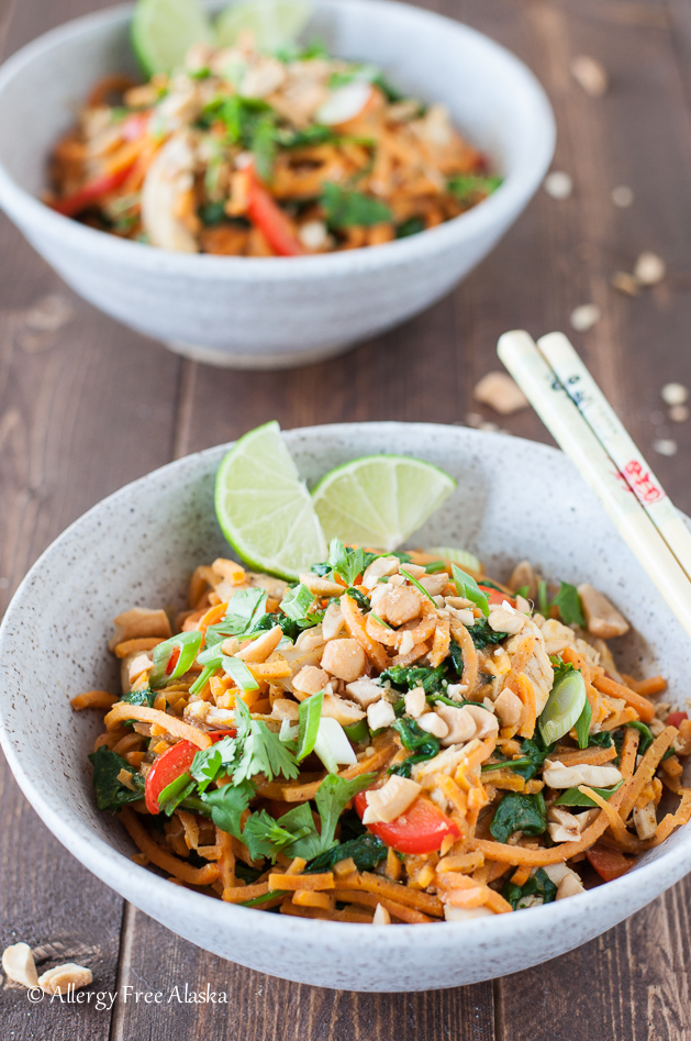 a bowl filled with sweet potato noodles, chicken, spinach, chopped cashews, and lime wedges