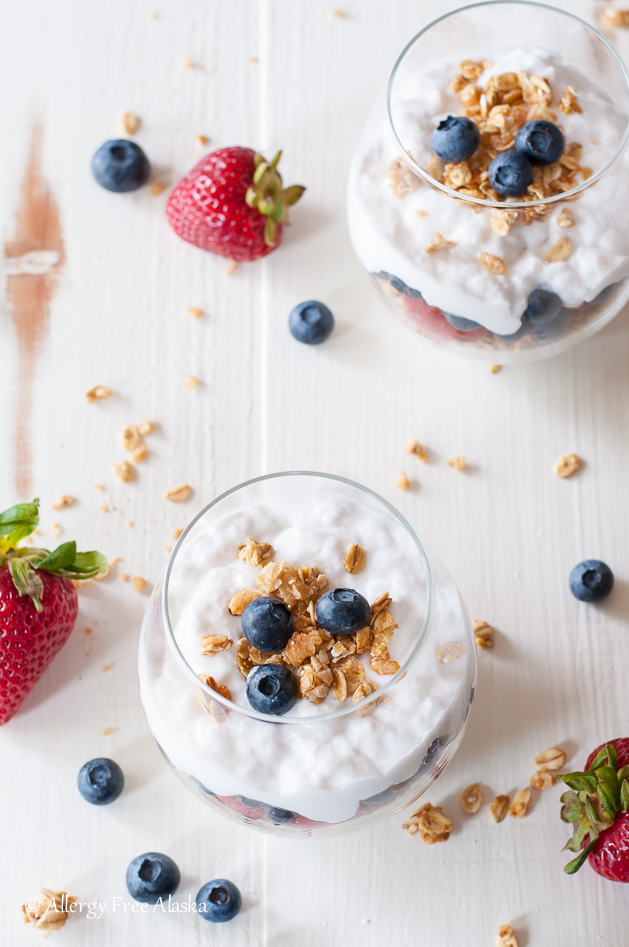 2 instant pot coconut milk yogurt parfaits sitting on white background, with berries and granola sprinkled on background (shot at different angle)