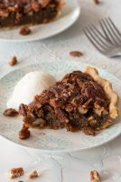 slice of pecan pie on plate with scoop of ice cream