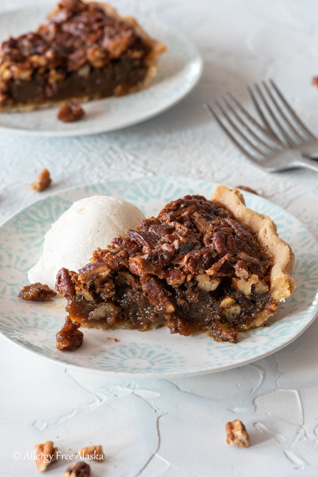 slice of gluten free pecan pie sitting on plate with scoop of ice cream