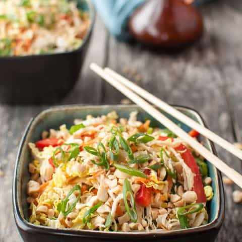 a bowl of a colorful cabbage salad with chicken and green herbs with chopsticks