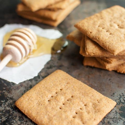 graham crackers scattered on a dark countertop aside a honey dipper dipped in honey