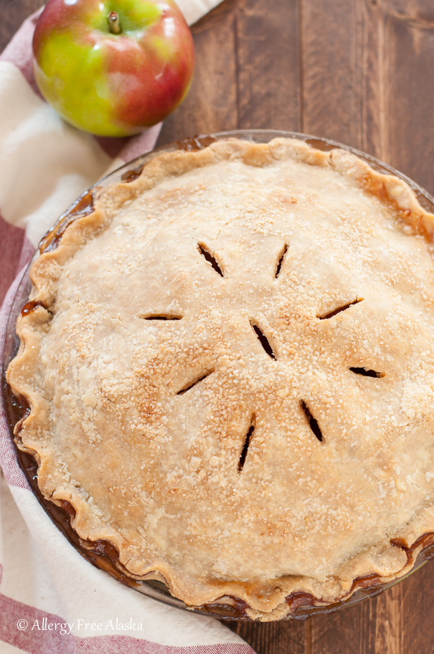 baked whole vegan apple pie, on dark brown background, with cream and red kitchen towel and apple