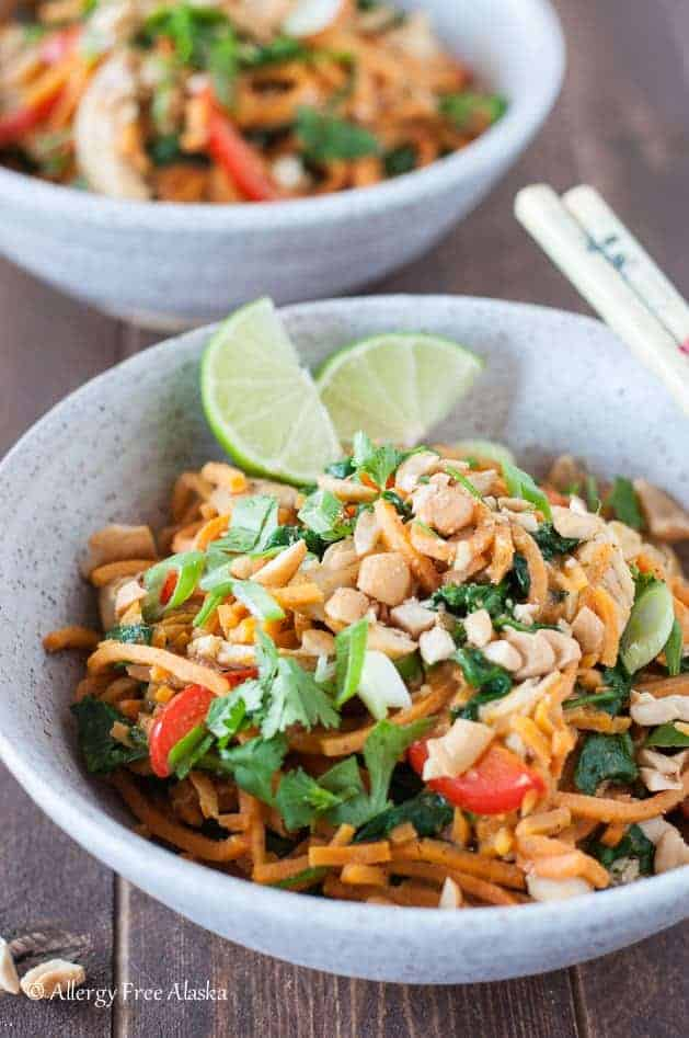 thai chicken sweet potato noodle bowl with lime wedges and chop sticks