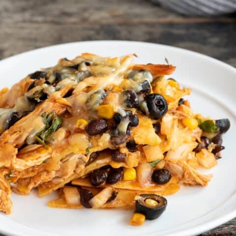 piece of gluten free chicken enchilada casserole sitting on white plate