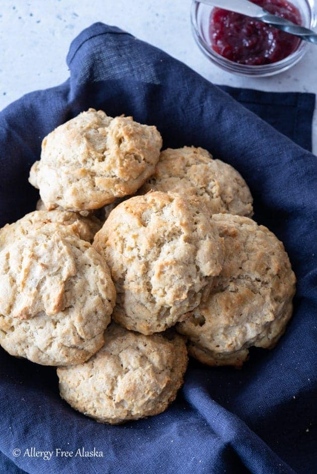 gluten-free biscuits sitting in blue napkin lined basket, with small bowl of jam off to side