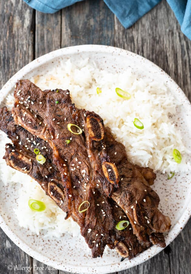 Top down view flanken ribs on pile of rice sitting on speckled brown and white plate