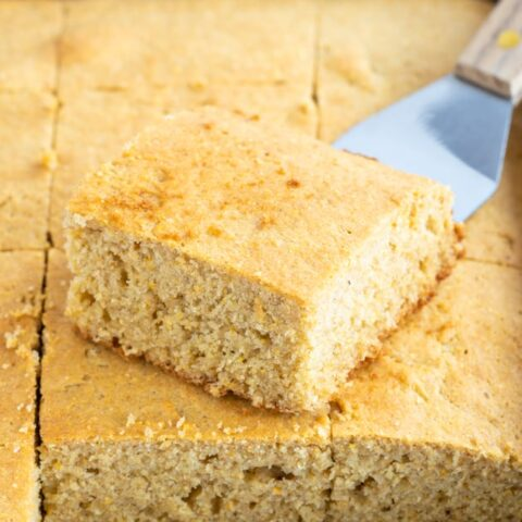 pan of sliced gluten-free cornbread with spatula holding 1 piece