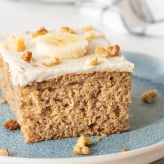 slice of gluten free cake topped with a banana slice and chopped walnuts