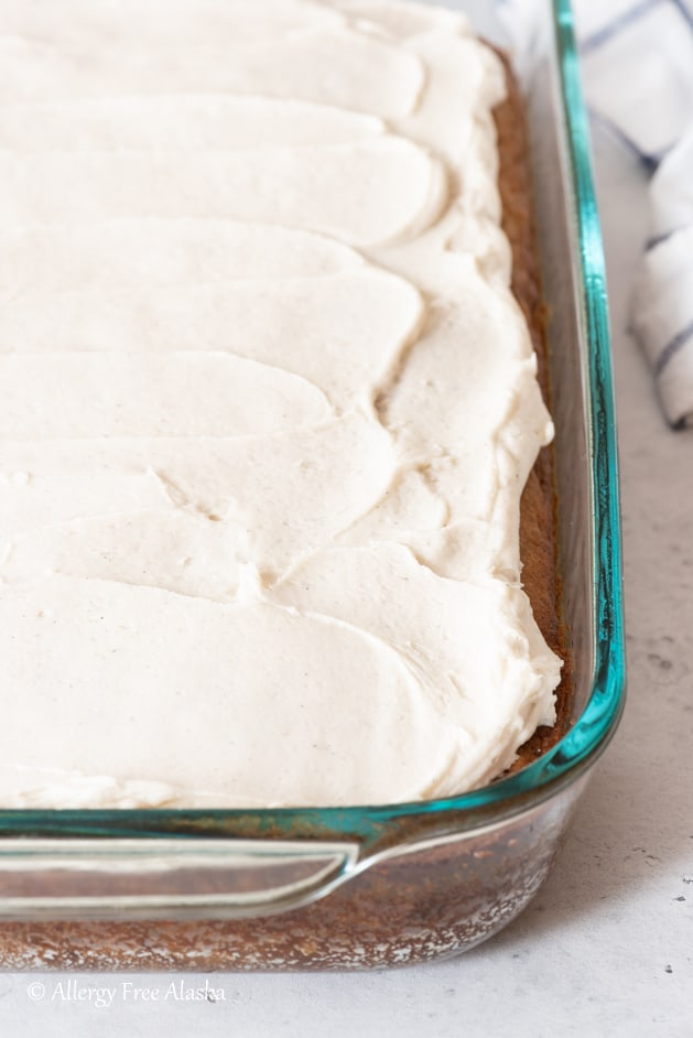 frosted gluten-free banana cake in glass pan sitting on light gray background