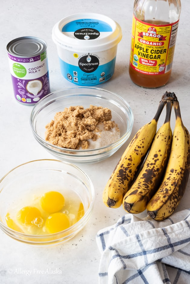 gluten free banana cake ingredients laid out on light gray background