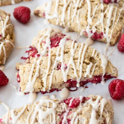 gluten free raspberry scones sitting on pastry board at different angle