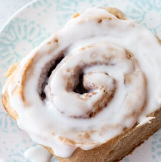 top down view of an iced gluten-free cinnamon roll sitting on blue and white plate
