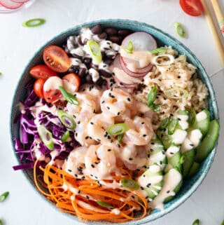 Top down view of shrimp poke bowl on white background sprinkled with green onion and cherry tomato halves