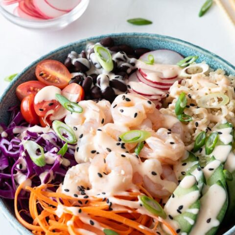 Blue bowl filled with brown rice, shrimp, carrots, cabbage, and other fresh ingredients sitting on white background
