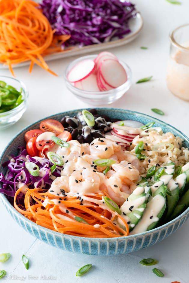 Side angle of shrimp poke bowl with Sriracha mayo on white background with sliced raddish, carrot ribbons, and sliced purple cabbage in background