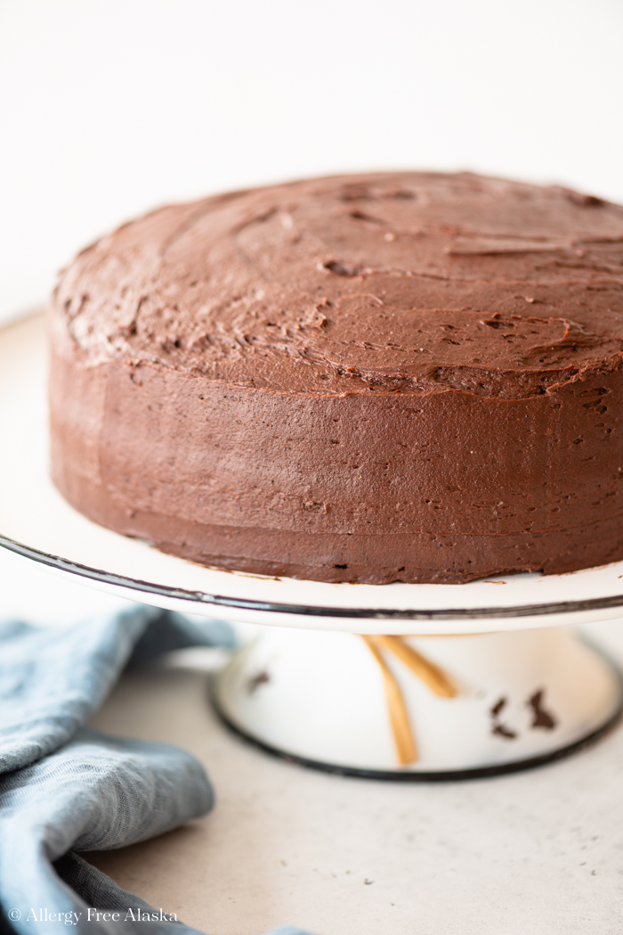 at different angle: chocolate frosted cake on white cake stand sitting on light gray background with blue napkin