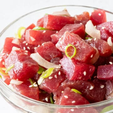side view of poke salad in clear bowl on white background