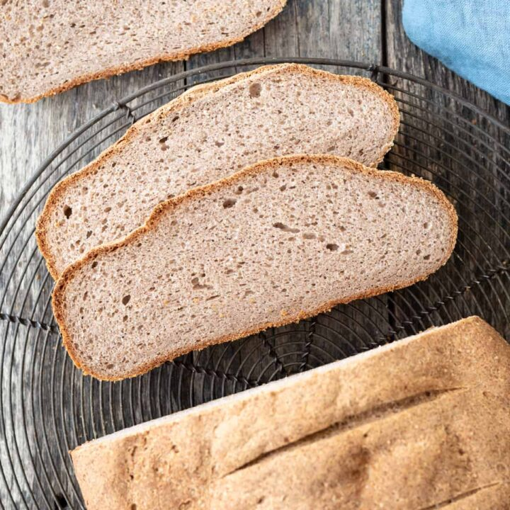 top down view of half sliced buckwheat bread sitting on wire cooling rack on gray/blue background