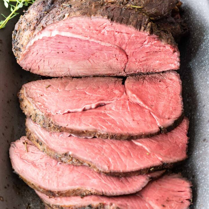 top down view of partially sliced sirloin tip roast sitting on gray platter with handful of fresh thyme